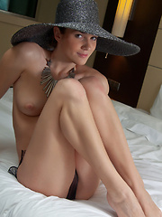 Wearing a broad brimmed hat, a chunky piece of necklace, and a sheer black panty