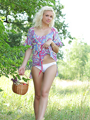 Gorgeous blonde teen chick with a basket of peaches taking off clothes outdoor on the nature.