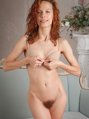 Dennie strips on the couch baring her petite body and unshaven pussy.